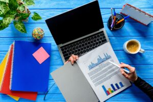 Close-up view of person studying charts by laptop on blue wooden table with stationery